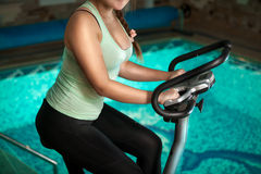 Girl riding exercise riding bike at swimming pool Royalty Free Stock Photography