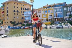 Girl riding a foldable e-bike in a Port. Girl riding a foldable e-bike in a Mediterranean marina port ebike stock images