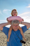 girl riding on grandpa's shoulders Stock Photography
