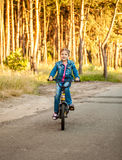 Girl riding her bike on road at forest Royalty Free Stock Images