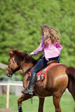 Girl riding her brown horse in a training field Stock Images