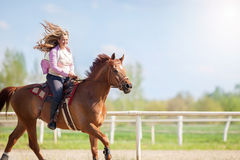 Girl riding her brown horse in a training field Royalty Free Stock Photo