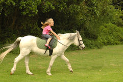 Girl riding her pony. A cute little caucasian blond girl child with happy smiling facial expression riding her white pony in the park outdoors Royalty Free Stock Images
