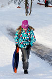 Girl riding with hills on sleds Stock Photography