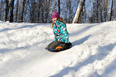 Girl riding with hills on sleds Royalty Free Stock Image