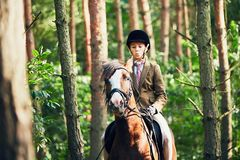 Girl riding a horse in forest. Teenage girl in formal wear riding a horse in forest Stock Photography