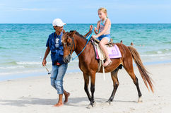 Girl riding horse. Horse owners and little girl riding horse for rent along the beach. HUAHIN beach in Thailand Royalty Free Stock Photography