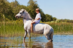 Girl riding a horse in a river Stock Photo