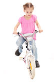 Girl riding kids bike. Girl riding bicycle. Isolated on white Royalty Free Stock Photography
