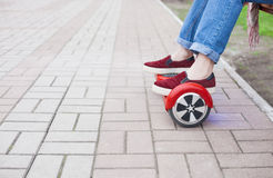 Girl riding on modern red electric mini segway or hover board scooter Royalty Free Stock Image