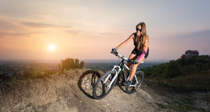 Girl riding on the mountain bicycle against evening sky Stock Images