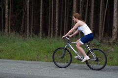 Girl riding mountain bike through forest Stock Photography