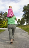 Girl riding piggyback. Obese mother walking with daughter on shoulders Stock Images