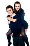 Girl riding piggyback and embracing boy tightly Stock Image