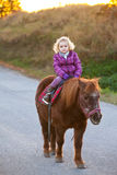 Girl Riding a Pony - baby Ride a Horse Royalty Free Stock Image