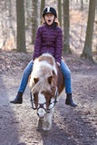 Girl riding a pony. Young girl riding a pony/horse in the forest in Denmark Royalty Free Stock Images