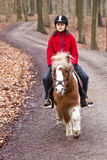 Girl riding a pony. Young girl riding a pony/horse in the forest in Denmark Stock Photos