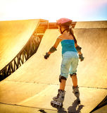 Girl riding on roller skates in skatepark. Backlit on background. Royalty Free Stock Image
