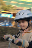 Girl riding a scooter. A young girl with a helmet on is riding a scooter. The background is blurred showing motion Royalty Free Stock Image