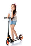 Girl riding a scooter Stock Photos