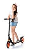 Girl riding a scooter Stock Photos