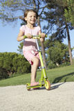 Girl Riding Scooter In Park Stock Photos