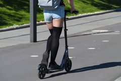 Girl riding a scooter in the summer in the park stock photos