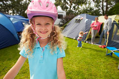 Girl Riding Scooter Whilst On Family Camping Holiday Stock Images