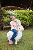 Girl riding sheep. The girl is riding the sculpture sheep stock photo