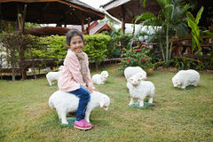 Girl riding sheep. The girl is riding the sculpture sheep royalty free stock photos