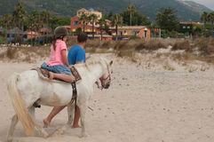 A girl riding a small horse with a trainer Royalty Free Stock Image