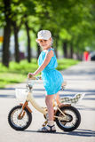 Girl riding on small two-wheeled bicycle Stock Images