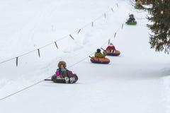 Girl riding snow tube stock photos