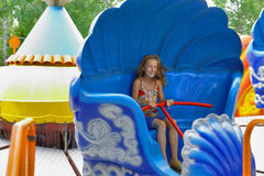 Girl riding on a spinning ride Stock Image