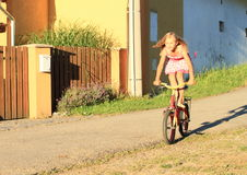 Girl riding and standing on a bike Stock Images