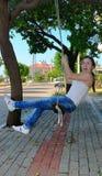 A girl riding a swing and screams Stock Photos
