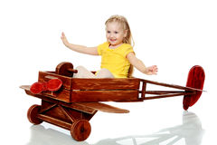 Girl is riding a toy plane. Stock Images