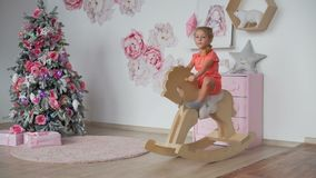 Girl riding toy rocking horse near christmas tree. Little girl riding toy rocking horse in the room in pink colors near the christmas tree stock footage