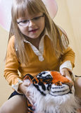 Girl riding toy tiger Stock Photos