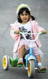 Girl riding tricycle Stock Image