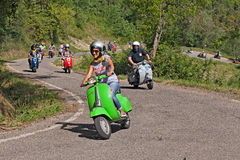 Girl riding vintage scooter Vespa Stock Photo