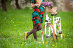 Girl riding vintage white bicycle with flowers basket Stock Image
