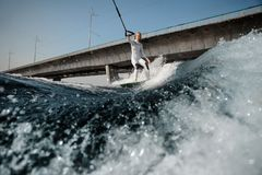 Girl riding on the wakeboard holding a rope royalty free stock photos