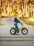 Girl riding yellow bike at forest Stock Photos