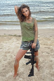Girl with a rifle on the beach Stock Photos
