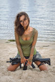 Girl with a rifle on the beach Stock Image