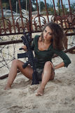 Girl with a rifle on the beach. Sexy girl with a rifle on the beach Stock Image