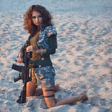 Girl with a rifle on the beach Royalty Free Stock Images