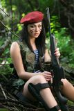 Girl with a rifle in the woods Stock Photography