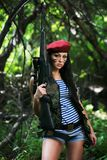 Girl with a rifle in the woods stock images